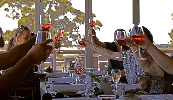 A group of friends enjoying lunch raise their glasses of Rose